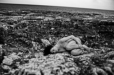 Woman lying in between rocks - p8850281 by Oliver Brenneisen