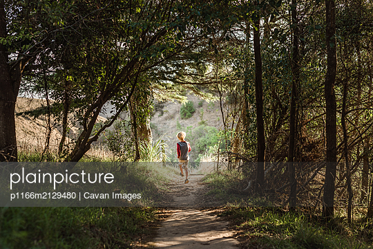 Young boy skipping on a trail in the forest - p1166m2129480 by Cavan Images