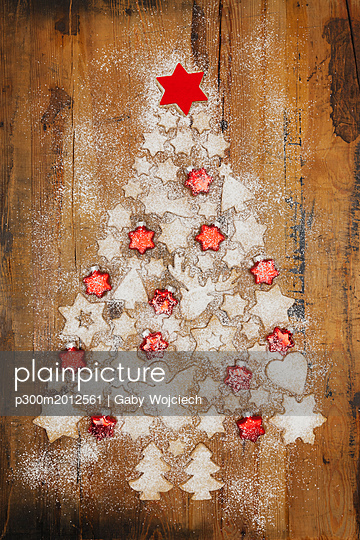 Christmas cookies and red star-shaped Christmas baubles forming Christmas Tree on wooden background