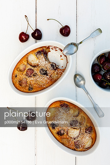 Bowls of gluten free homemade clafoutis with cherries, peaches and almonds - p300m2154786 by Eva Gruendemann