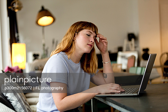 Portrait of pensive young woman sitting in a coffee shop using laptop - p300m2156072 by FL photography