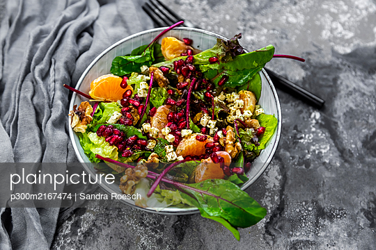 Winter salad with lettuce, tangerines, walnuts, feta and pomegranate seeds - p300m2167474 by Sandra Roesch