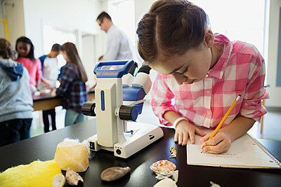 Schoolgirl taking notes at microscope science laboratory classroom - p1192m1019881f by Hero Images