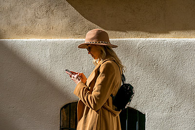 Fashionable young woman at a building using cell phone - p300m1562471 by VITTA GALLERY