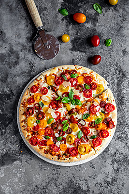 Sliced pizza with tomatoes and basil leaves - p300m2024216 von Sandra Roesch