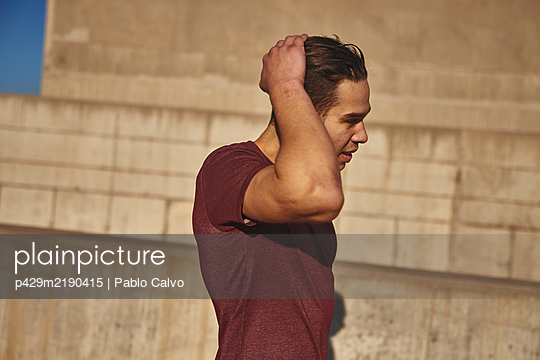 Portrait of young man standing in front of concrete wall in Barcelona, Catalonia, Spain. - p429m2190415 by Pablo Calvo