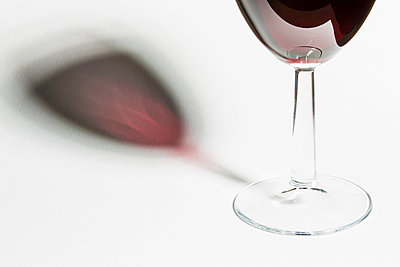 Glass full of red wine against white background - p1057m1564500 by Stephen Shepherd