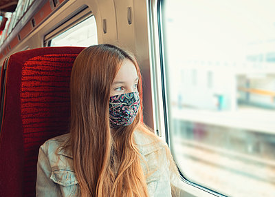 young teenager travelling on a train with mask looking out the window - p1166m2247964 by Cavan Images