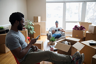 Young couple with smart phones relaxing, taking a break from packing, moving house - p1192m1559948 by Hero Images