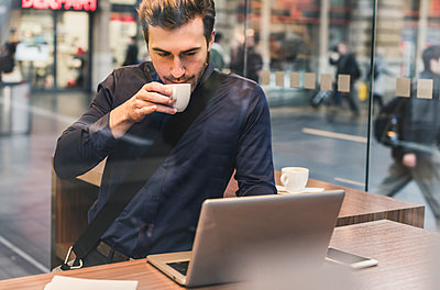 Young businessman in a cafe at train station with cup of coffee and laptop - p300m1562878 by Uwe Umstätter
