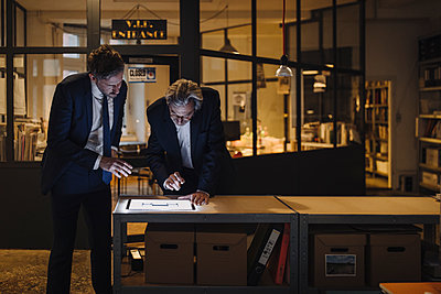 Two businesssmen with shining tablet talking in office - p300m2154897 by Gustafsson