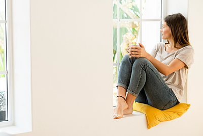 Smiling young brunette woman at home sitting on window bench and holding a coffee mug while looking outside - p300m2180594 by Steve Brookland
