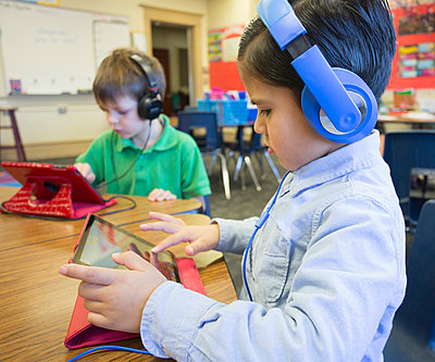 Caucasian students using digital tablets in classroom - p555m1305669 by Hill Street Studios