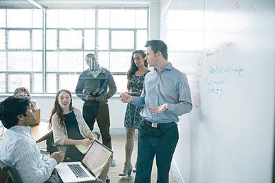 Businessman talking near whiteboard in meeting - p555m1504097 by John Fedele