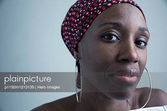 Close up portrait serious African American woman wearing gele headscarf and large hoop earrings - p1192m1213135 by Hero Images