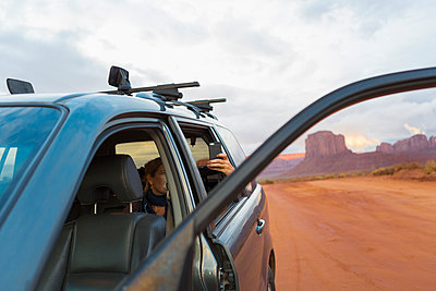 Caucasian girl taking cell phone photograph from car, Monument Valley, Utah, United States - p555m1420824 by Marc Romanelli
