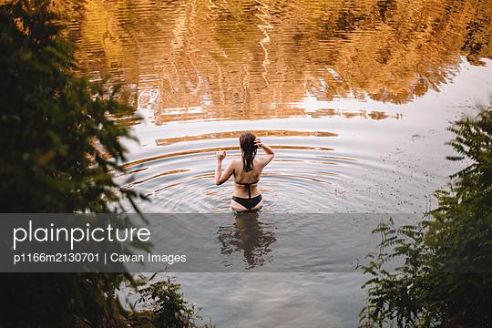 Rear view of sensual woman standing in lake - p1166m2130701 by Cavan Images