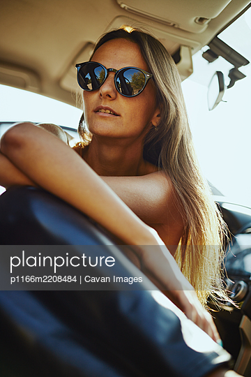 Close-up of a woman in sunglasses sitting in the car. - p1166m2208484 by Cavan Images