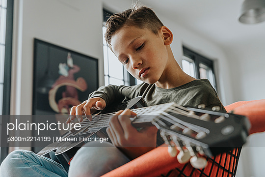 Close-up of boy playing guitar while sitting on chair at home - p300m2214199 by Mareen Fischinger