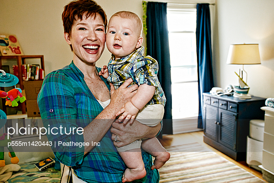 Caucasian mother holding baby in bedroom - p555m1420443 by Peathegee Inc