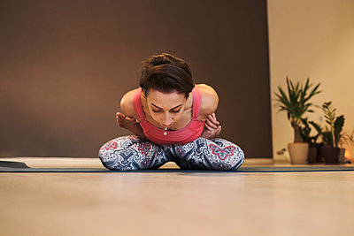 young woman doing yoga on yoga mat in atmospheric yoga studio - p1166m2177390 by Cavan Images