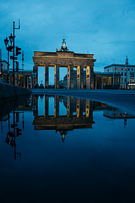 Germany, Berlin, view to  Brandenburg Gate reflecting in puddle by night - p300m1469903 by Michael Zwahlen
