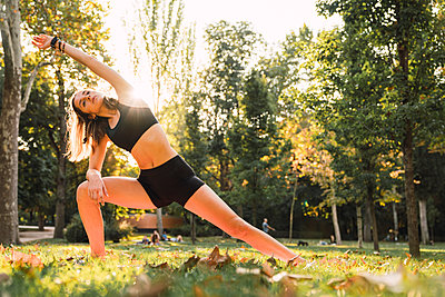 Fit young woman practicing yoga in a park - p300m2059078 von Kike Arnaiz
