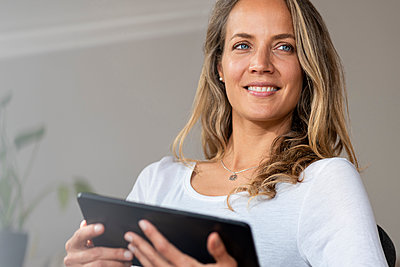 Smiling woman with blue eyes looking away while holding digital tablet at home - p300m2276379 by Steve Brookland
