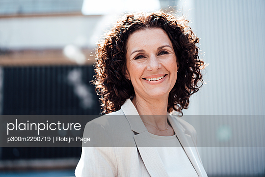 Smiling mature businesswoman in front of industry - p300m2290719 by Robijn Page