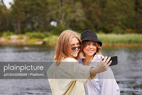 Two friends taking selfie at lakeside - p312m2299658 by Plattform