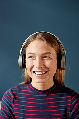 Young woman listens to music with headphones - p1124m1589224 by Willing-Holtz
