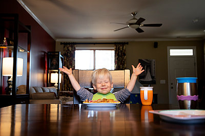 Portrait of a young boy eating food while sitting in a chair at home - p1480m2148161 by Brian W. Downs