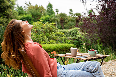 Smiling woman with eyes closed relaxing while sitting on chair in garden - p300m2287109 by VITTA GALLERY