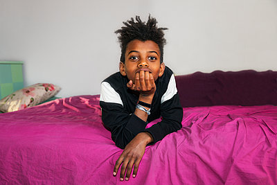 Boy on bed looking at camera - p312m2139403 by Pernille Tofte