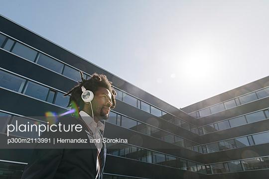 Businessman wearing headphones in the city - p300m2113991 von Hernandez and Sorokina