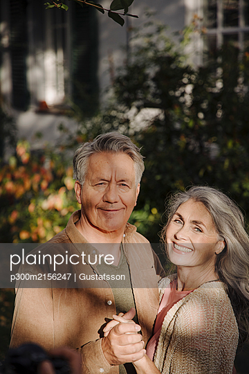 Portrait of happy senior couple in garden of their home in autumn - p300m2156247 by Gustafsson