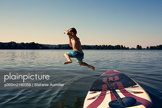 Boy jumping from SUP board into lake at evening twilight - p300m2180358 by Stefanie Aumiller