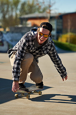 Male skateboard enthusiast rolling around concrete skatepark - p1362m1553696 by Charles Knox