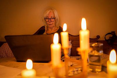 Woman at laptop by candle lights - p1418m2254186 by Jan Håkan Dahlström