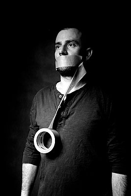 Man with adhesive tape on his mouth - p1521m2150052 by Charlotte Zobel