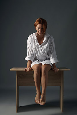 Redhaired woman sitting on a table  - p1561m2134584 by Andrey Cherlat