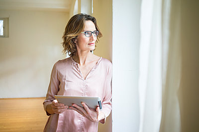 Mature woman in empty room holding tablet at the window - p300m1563099 by Robijn Page