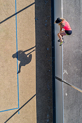 Aerial view of sportive woman jumping over barrier - p300m2005368 von Stefan Schurr