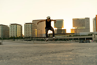 Young man doing a skateboard trick in the city at sunset - p300m2028708 by VITTA GALLERY