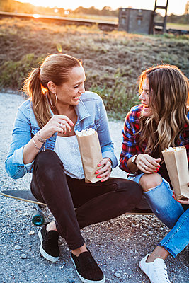 Two laughing friends sitting on longboard eating popcorn - p300m2083335 von Epiximages