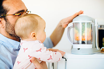 Father and baby daughter pureeing baby food in food processor - p429m1417907 by Sofie Delauw