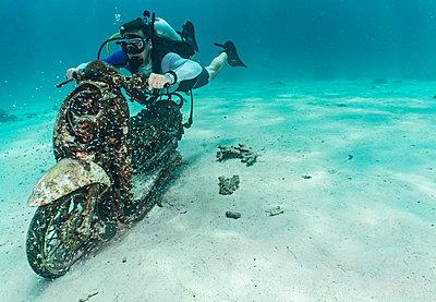 Diver posing with submerged motorbike, Ko Racha Yai, Rawai, Phuket, Thailand - p924m2097818 by Henn Photography