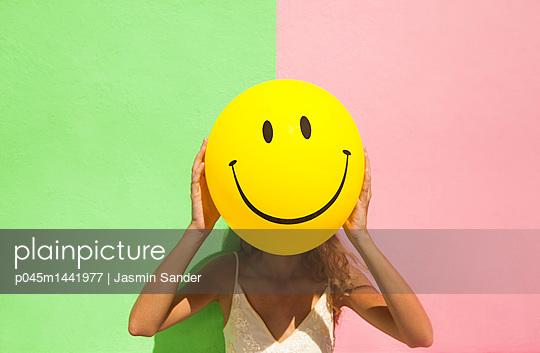 Smiley vor grün-rosa Wand - p045m1441977 von Jasmin Sander