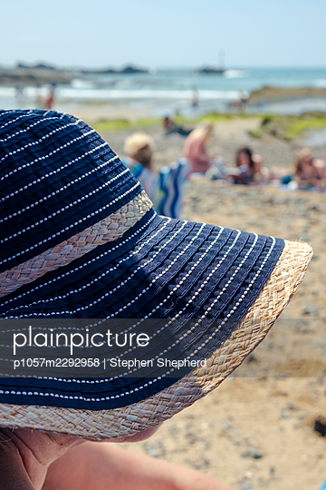 Woman with a sun hat on the beach - p1057m2292958 by Stephen Shepherd