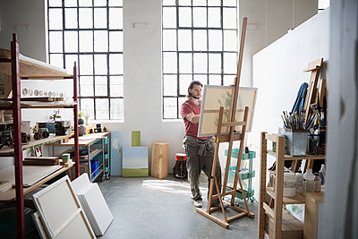 Male painter painting at canvas on easel in art studio - p1192m1490155 by Hero Images